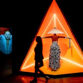 Visitor walking by orange-lit display of outfit in Gender Bending Fashion exhibition
